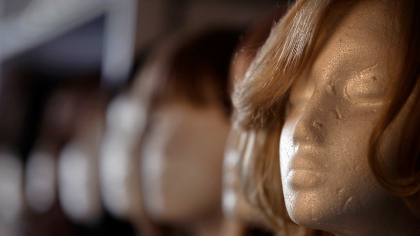 A close up of a styrofoam mannequin wearing a long brown wig.