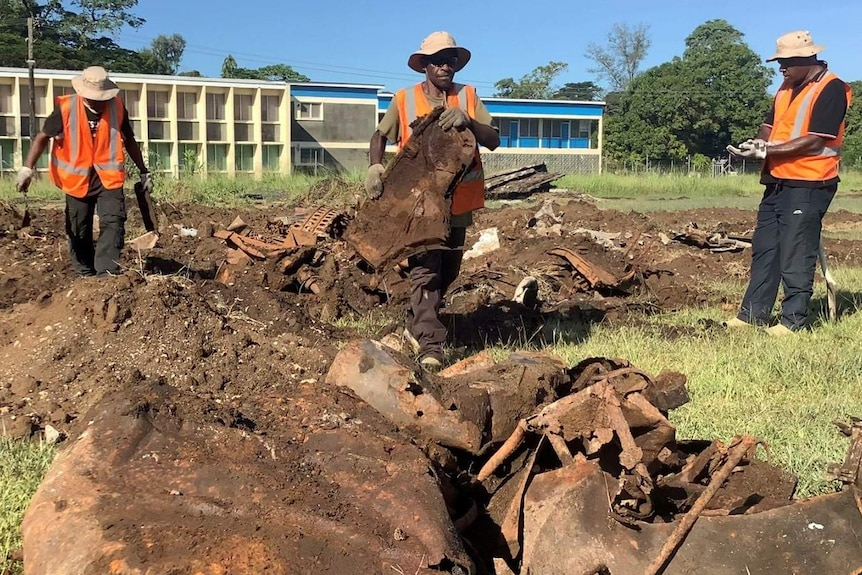 The UXO clearing team wearing hi-vis in a ground with plane debris.