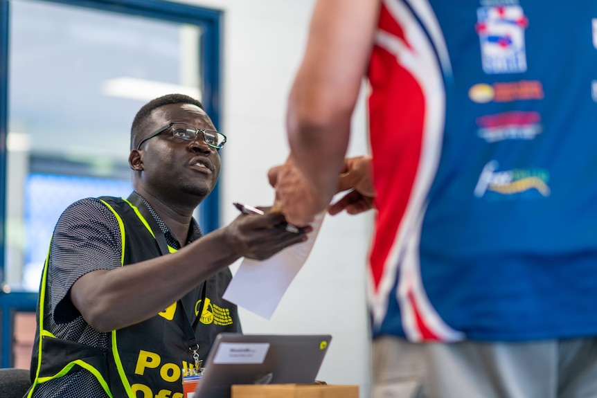 A seated man wearing a polling official vest handing a ballot paper to a man standing at his desk.