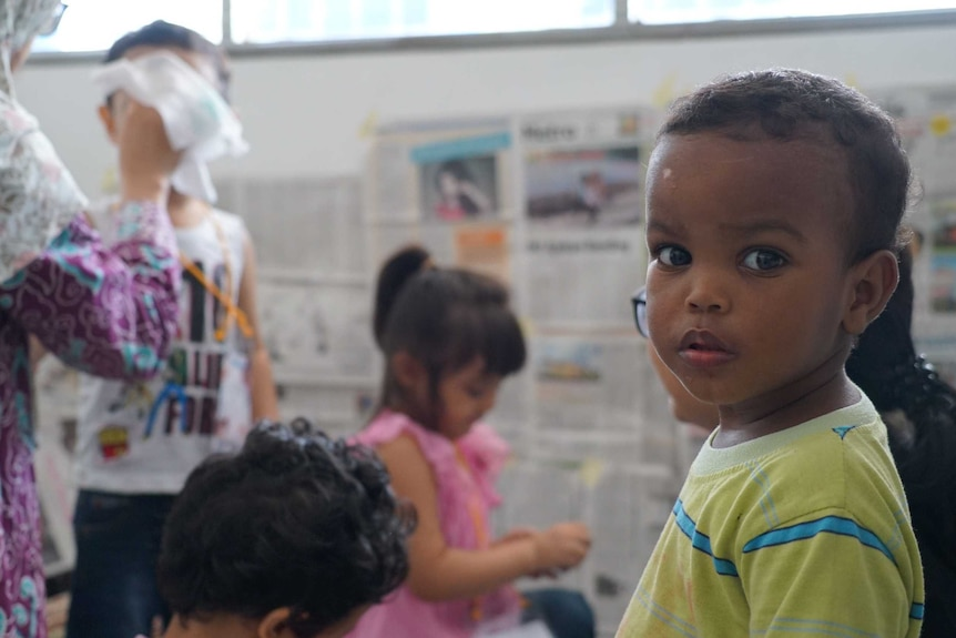 Children in the play room, covered with newspaper, in Jakarta Immigration Detention Centre.