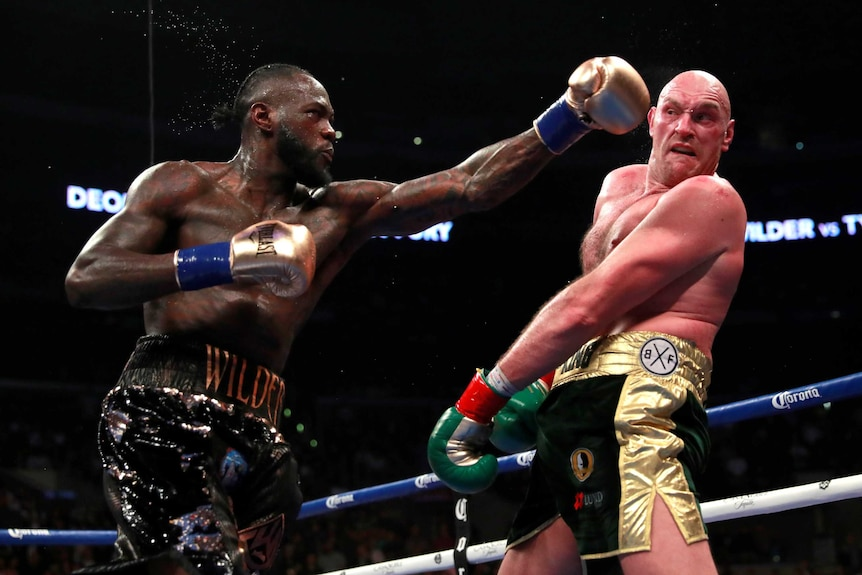 Deontay Wilder throws a punch with his left fist as Tyson Fury trys to avoid it.
