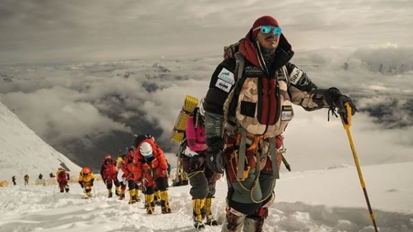 A line of mountaineers are seen in a single-file line down a white mountain peak.