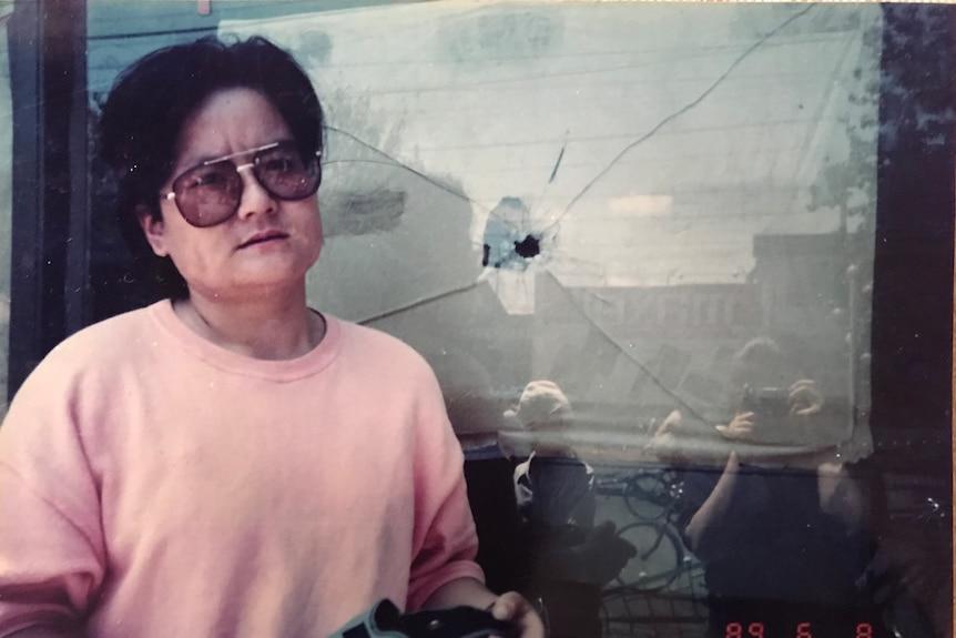 Liling Wang stands beside a bullet hole in a window in Beijing on June 8, 1989.