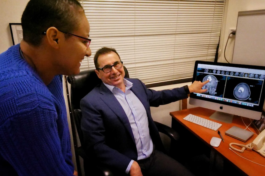 Dr Rogers points at a brain scan on a computer screen as Hare Haro looks on.
