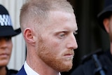 A ginger man leaves Bristol Crown Court with two police officers in the background.