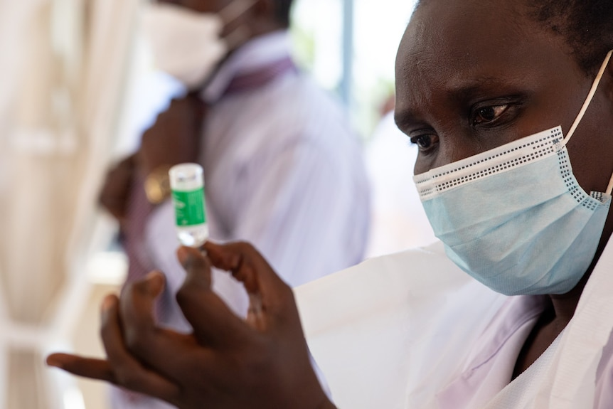 An African woman in a surgical mask holding a small vial between finger and thumb