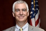 Fred Fleitz smiling, he is wearing a grey suit and is standing in front of an American flag.