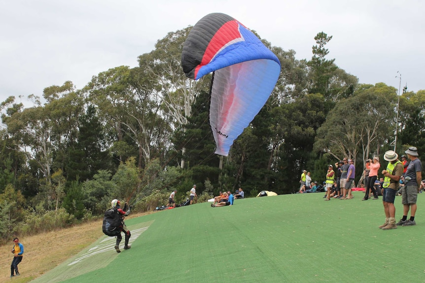 A man is about to take to the air after running down a steep hill.