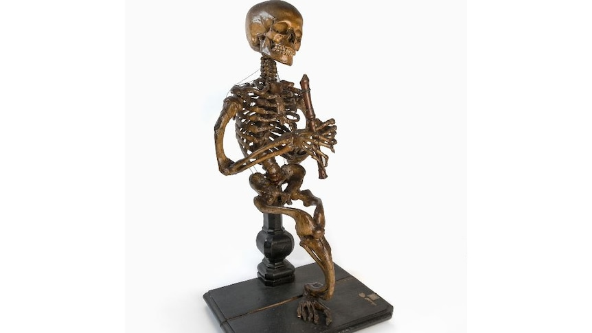 Gold-coloured skeleton with one leg tied to a seat, hands positioned around a gold flute in front of it