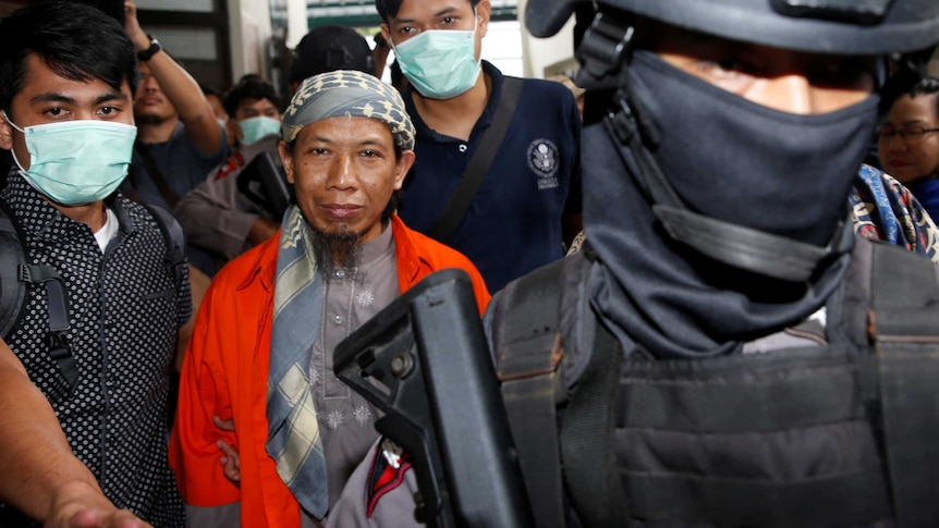 Policemen guard Islamic cleric Aman Abdurrahman during his walk to the courtroom.
