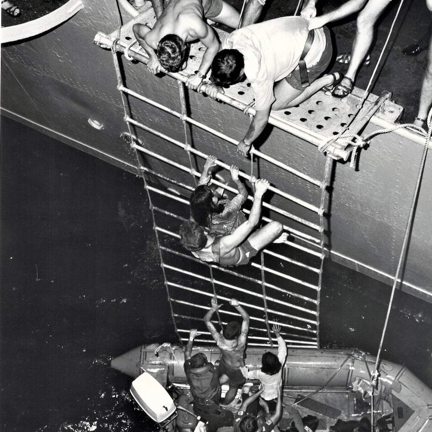 Vietnamese refugees rescued from the South China Sea, climbing up a roped ladder into a HMAS vessel.