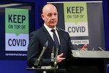 """Tasmanian Premier Peter Gutwein in a suit gestures at a press conference podium in front of a """"Keep on top of COVID"""" sign."""