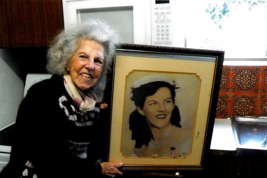 Mary Heather Lane holding a photograph of herself