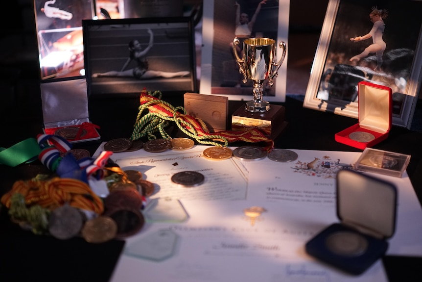 Medals, ribbons and certificates laid out on a table.
