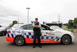 A highway patrol policeman stands in front of his cruiser with his arms folded.