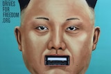A poster showing Kim Jong-un's face with a USB slot for a mouth.