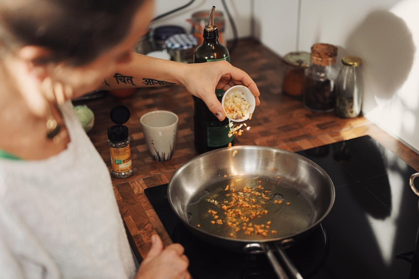 A woman tips ingredients into a frying pan