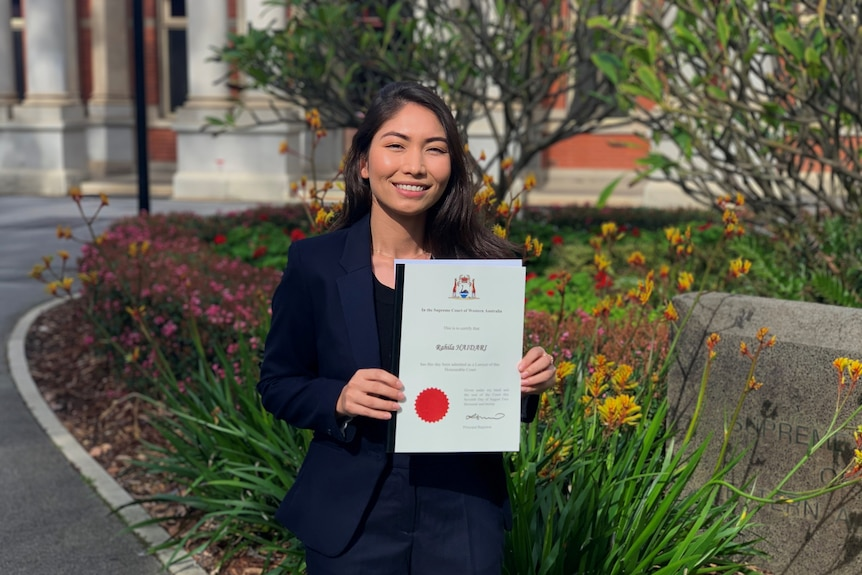 A woman stands in front of a garden holding a certificate.