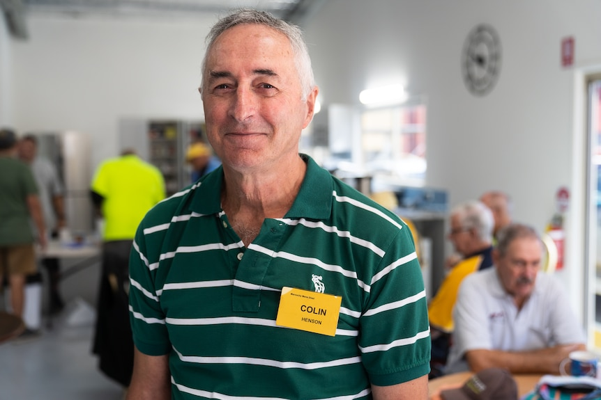 Man in a green shirt standing in front of tables of men having smoko in a men's shed, smiling kindly