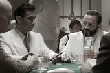 Well-dressed men in the 1930s talk at a poker table.