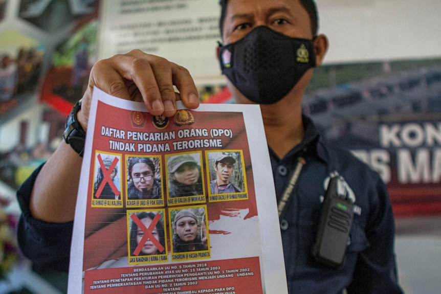 A police officer shows a wanted poster displaying the photos of two militants who were killed