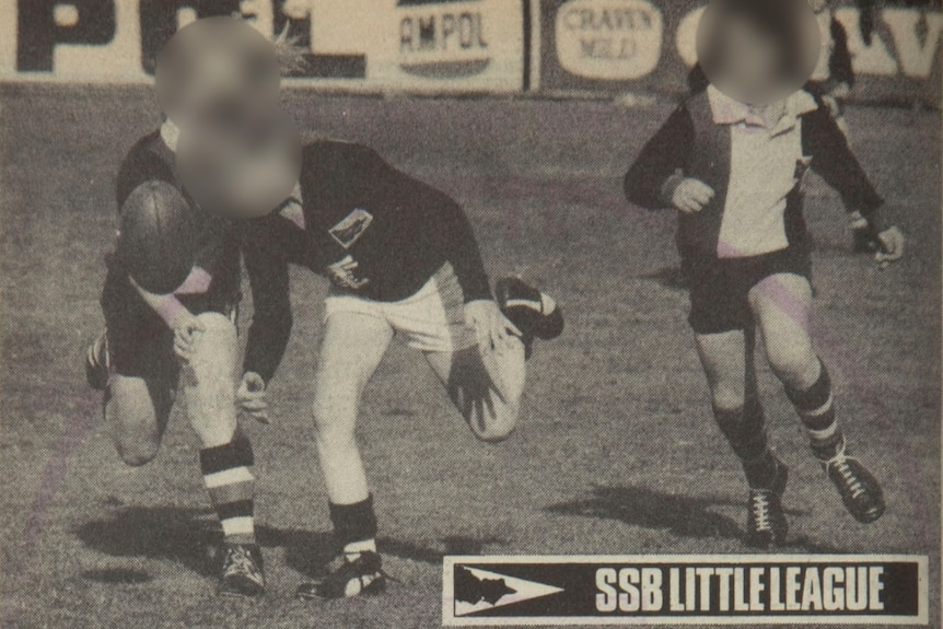 A black and white newspaper image of three boys in replica St Kilda uniforms playing Australian rules football.