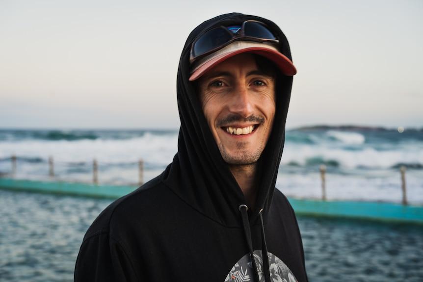 A man in a hoodie on a beach
