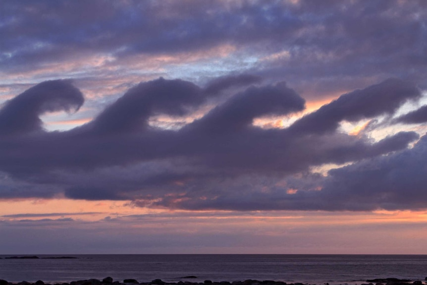 Four cloud waves break from left to right as sunrays colour the sky orange over a calm ocean