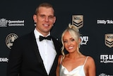 A Many Sea Eagles NRL player stands with his partner on the red carpet at the Dally M Awards.