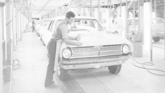 A man polishes the bonnet of a Holden car inside a factory in a production line.