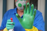 A man standing at his front door wearing cleaning gloves holds and holding a spray bottle holds his hand up.