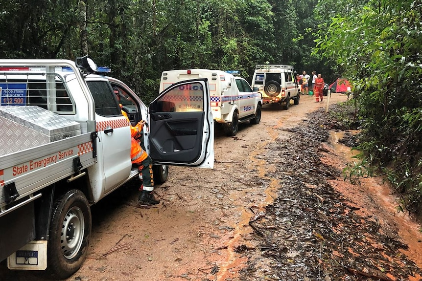 A line of emergency services vehicles on a muddy and wet dirt road in far north Queensland.