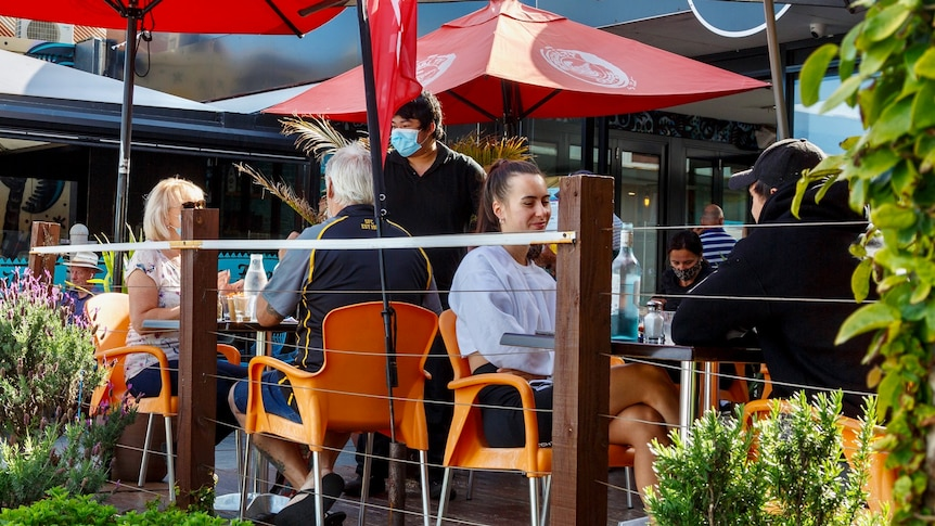 Patrons sit at a cafe in Melbourne as a waiter brings water to a table