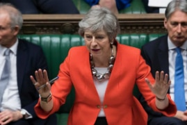 Theresa May addresses Parliament in a bright reddish orange jacket, with both hands up.