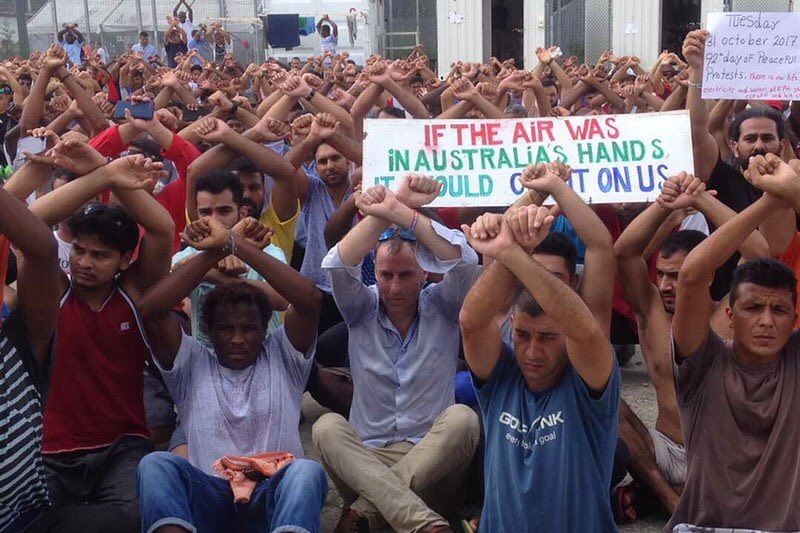 A large group of people sitting on the ground with their arms raised above their heads as if handcuffed.