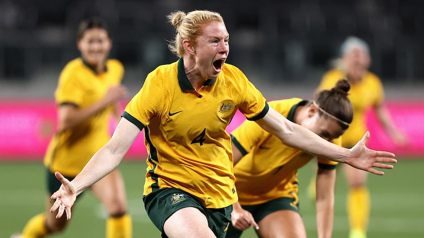 Clare Polkinghorne runs with her arms outstretched and mouth open