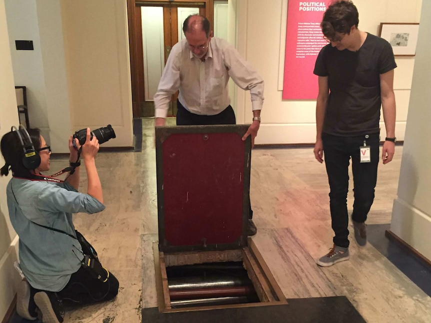 Sonya Gee holding a dsl camera as Michael Evans opens hatch to tunnel under Old Parliament House and Matthew Arnaudon watches.
