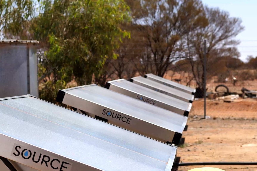 six solar hydro panel units lined up with trees in background