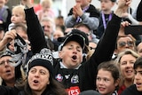 A crowd of Collingwood fans cheer and raise their hands at the AFL grand final parade.