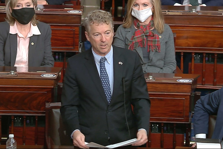 A white man in a suit stands to speak in the United States Senate.