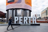 A woman wearing a face mask walks past the Yagan Square sign in Perth's CBD.
