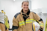 A woman in a firefighting uniform holds a helmet under her arm, smiling in the locker room.