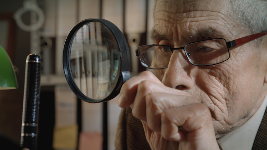 An elderly man with a magnifying glass, the spy Sergio Chamy in documentary The Mole Agent