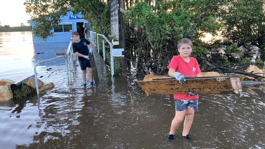 Two young boys carrying flood debris through flood waters from an oyster shed.