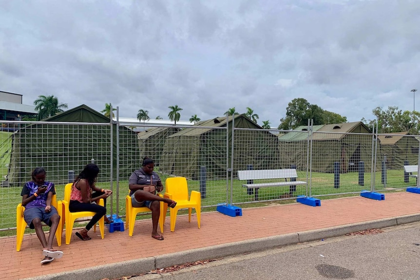 People sit on chairs in front of a fenced tent community.