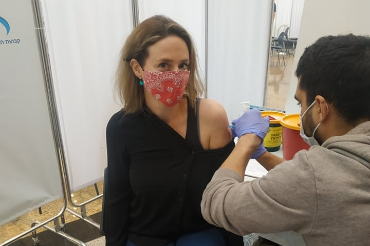 A woman in a red face mask receives an injection