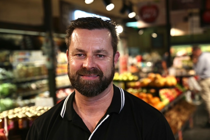 Craig Williams stands in the fruit and veg section of the supermarket he manages.