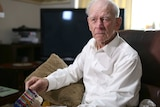 Former Kokoda soldier Bill Grayden sits in his lounge room holding his service medals.
