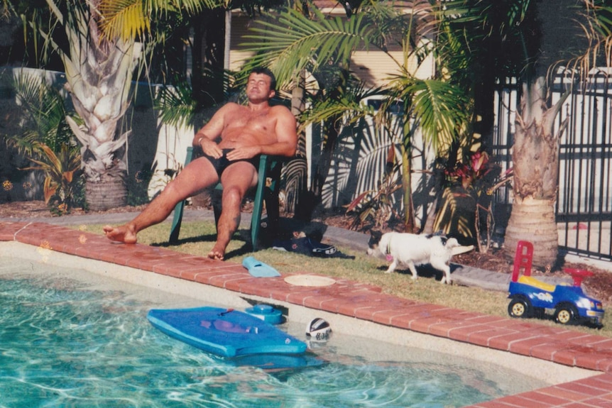 A man sits in a plastic outdoor chair and suns himself next to a swimming pool.
