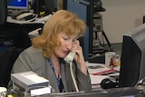 O'Neill on the phone at desk in newsroom.